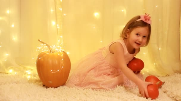 Princess girl with a crown on her head and a dress from a fairy tale about Cinderella. Child on the background lights with pumpkins.