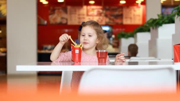 Dítě dívka jíst fast food hranolky a pití šťávy v kavárně