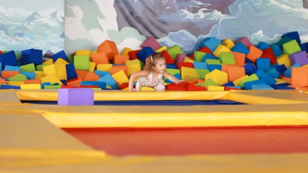 Baby girl jumping on a trampoline and playing on a childrens playground. Games for children.