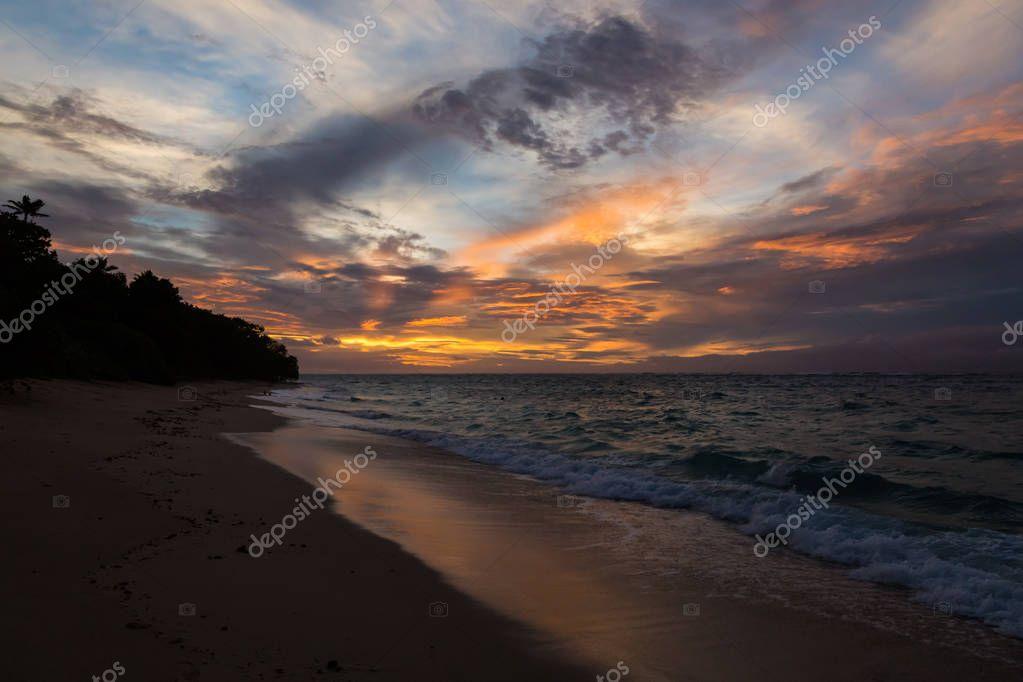 Twilight evening sunset. Waves, surf, swash at empty beautiful sandy beach on Foa island, Haapai islands or Ha'apai group, Tonga, Oceania, South Pacific Ocean. Near Lifuka.