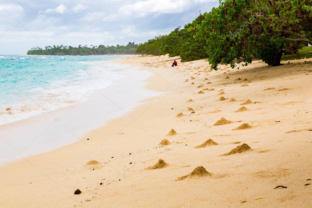Shore of an azure, turquoise, blue lagoon. Heaps of sand near crab hole minks. Waves, surf, swash at empty beautiful sandy beach, Foa island, Lifuka, Haapai group, Tonga, Oceania, South Pacific Ocean.