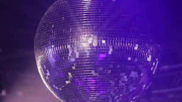 Zrcadlová disko koule na večírku. Otáčí, což odráží paprsky světla, svítidla.