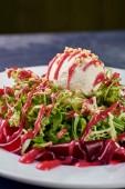 Egy szokatlan modern alacsony kalóriatartalmú saláta. A labda a ultramodern sózott fagylalt a saláta, a molekuláris konyha. Előétel a Zöldek, cékla, szósz, kecskesajt, buggyantott tojás és diófélék.