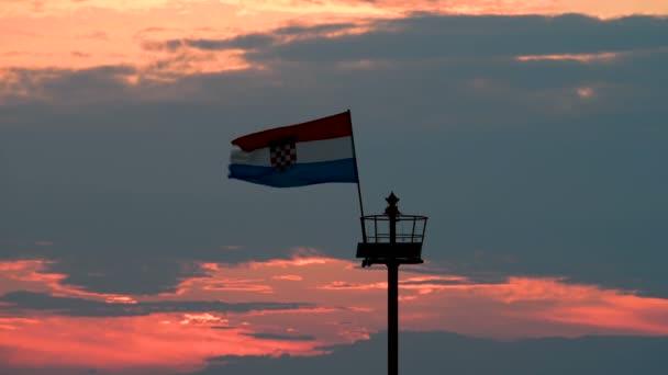 Molo di pietra con il faro e battenti bandiera nel tramonto
