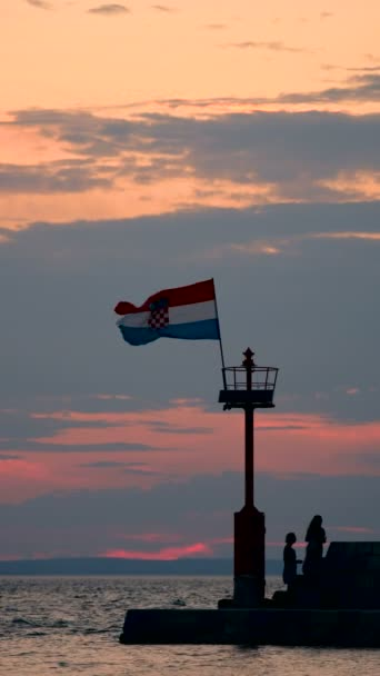 Molo con faro e battenti bandiera nel lasso di tempo tramonto di pietra, persone a piedi, arrampicata e seduto sul muro di pietra, verticale