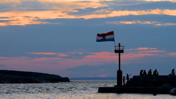 Stone pier with lighthouse and flying flag in sunset slow motion, people walking and sitting on stone wall