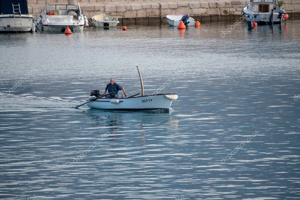 Fisherman in small traditional boat entering the harbor of Vinjerac, Croatia