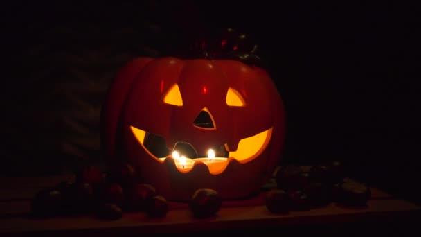 Halloween dýně od tmavé pozadí s kaštany