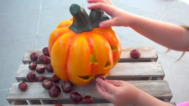 Malá holčička hraje krmení kaštany na halloween dýně