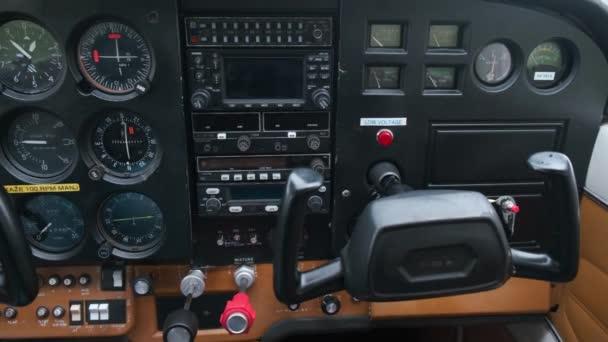kleines Kind spielt Pilot in der Kabine von Leichtsportflugzeugen, Kindheitsträume vom Fliegen, Nahaufnahme der Instrumententafel und Bewegung der Bedienelemente
