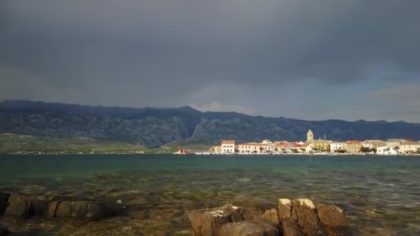 Časová prodleva pobřežního města v Chorvatsku, horách a mračen v pozadí, panoramatický pohled na malou vesnici a přístav