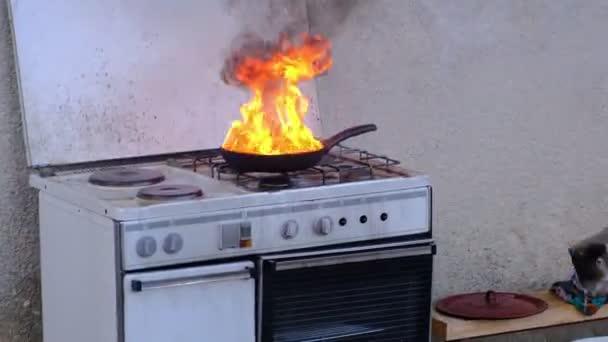 Hořící tuk exploduje v pánvi při styku s vodou, kuchyňský oheň demonstrace