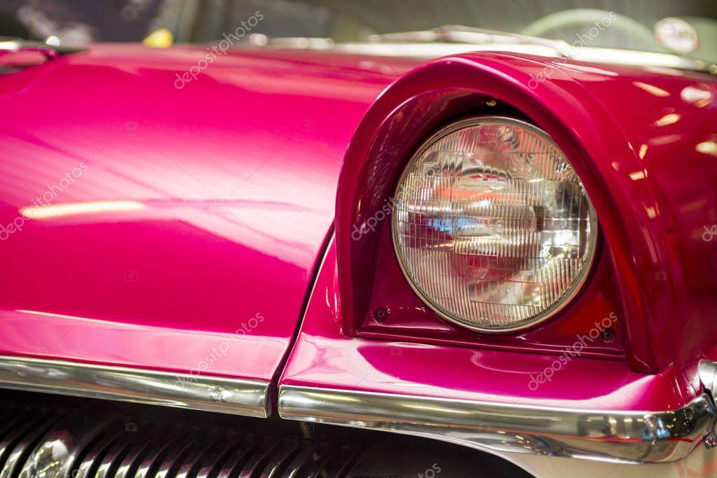 Headlight lamp vintage car. Classic car headlight. Close-up of headlights of orange vintage car. Exhibition