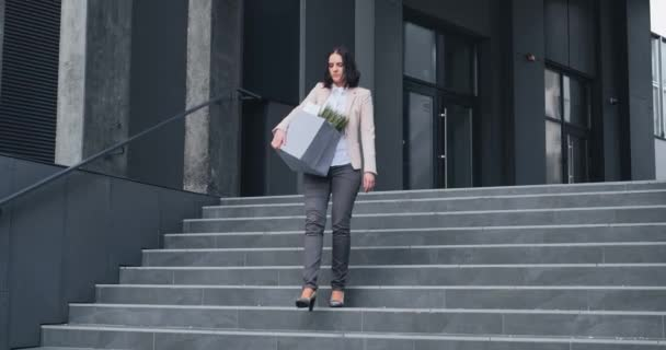 Dismissal of the manager. Woman in stress due to dismissal from work. Dismissed employee leaves the office with a belongings in box