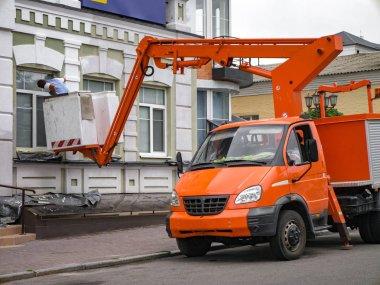 İşçi yenilemek yardımıyla modern parlak turuncu hava erişim platformu, bina cephe.