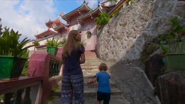 view of young woman with cute boy in beautiful ancient place with colored buildings in Thailand
