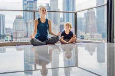 Mom and son practicing yoga on balcony with big city background. Mum and child doing exercises together, healthy family lifestyle concept.