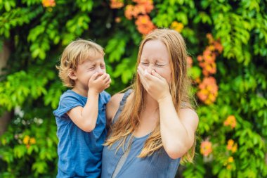 Mom and son sneeze in the park against the background of a flowering tree. Allergy to pollen concept.