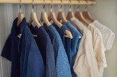 Oblečení na ramínkách v kabinetu přechodu od bílé do tmavě modrá