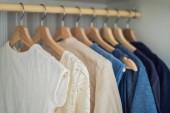 Fotografie Oblečení na ramínkách v kabinetu přechodu od bílé do tmavě modrá