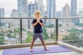 Fotografie Šťastný chlapec je praktikování jógy na terase s panoramatickým výhledem velkoměsta
