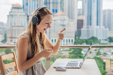 Young woman teaches a foreign language or learns a foreign language on the Internet on her balcony against the backdrop of a big city. Online language school lifestyle.