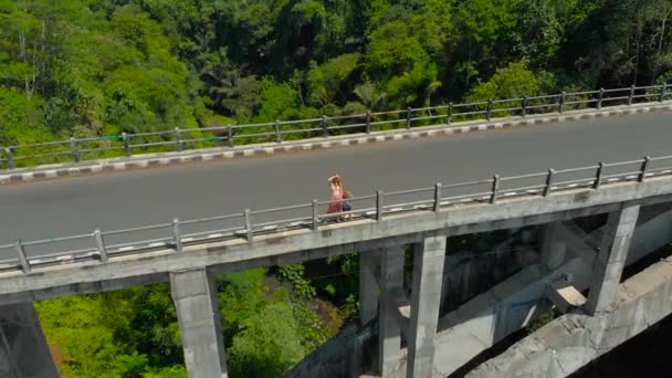 Aerial shot of a woman and her son standing on a tall bridge crossing a canyon with a river on its bottom in tropics. Mother shows something to the boy.