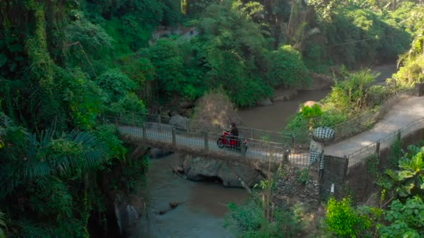 Bali Indonesia - May 15, 2018: aerial shot of a small bridge over the river with a small local temple on it in Bali, Indonesia. People on motorbikes crossing the bridge