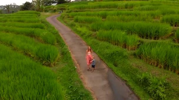 Mladá žena a syn společně pěšky podél rýžové terasy na ostrově Bali