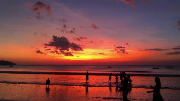 gyönyörű naplemente a tengerparton a Jimbaran falu sziluettek emberek. Bali, Indonézia