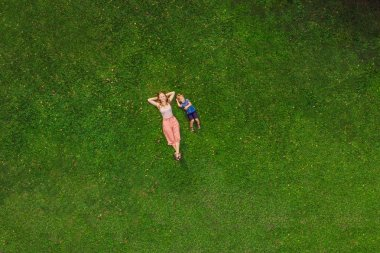 Mom and son are lying on the grass in the park, photos from the drone, quadracopter.