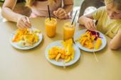 Mutter und Sohn sind Früchte und Saft in einem Café Essen.