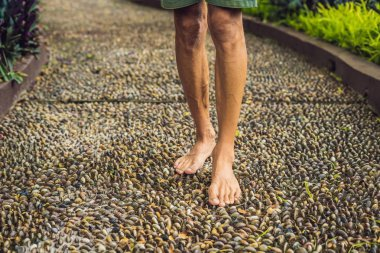 Man Walking On A Textured Cobble Pavement, Reflexology. Pebble stones on the pavement for foot reflexology.
