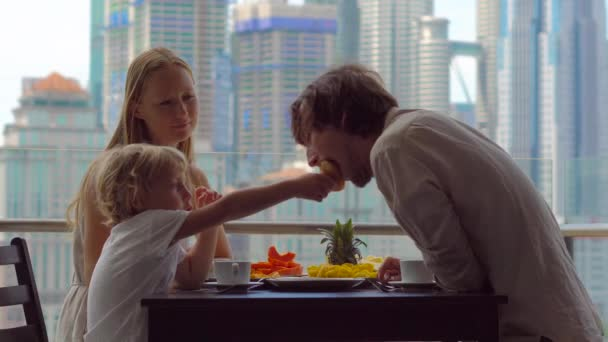 Young family having a breakfast, lunch on their balcony in a skyscraper with a view on a whole downtown of the city