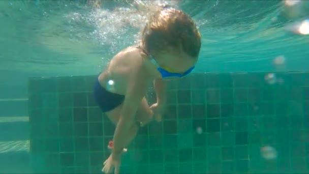 Slowmotion Aufnahme des kleinen Jungen Tauchen und Planschen im pool