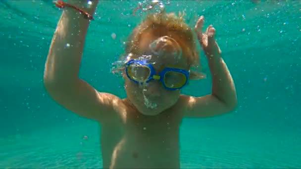 Zeitlupenaufnahme eines kleinen Jungen beim Tauchen und Blasen machen in einem Pool
