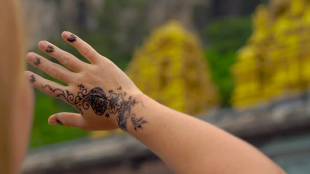 Young woman looking at her hand with a temporary henna hindu pattern