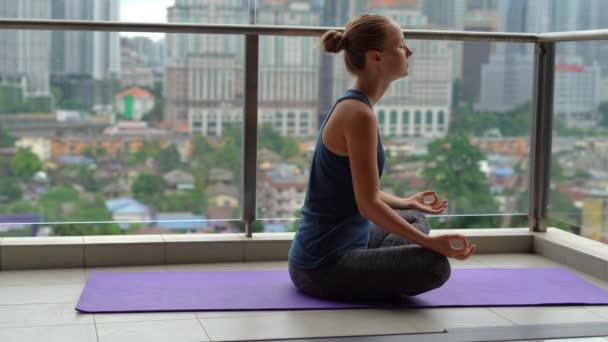 Mladá žena dělá cvičení jógy na balkóně v patrové budově s výhledem na centrum města s skycrappers. Duševní rovnováha v konceptu velkoměsta