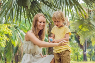 Mom and son use mosquito spray. Spraying insect repellent on skin outdoor.