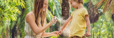 Mom and son use mosquito spray.Spraying insect repellent on skin outdoor. BANNER, long format