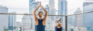 Mom and son are practicing yoga on the balcony in the background of a big city. Sports mom with kid doing morning work-out at home. Mum and child do the exercises together, healthy family lifestyle concept. BANNER, long format