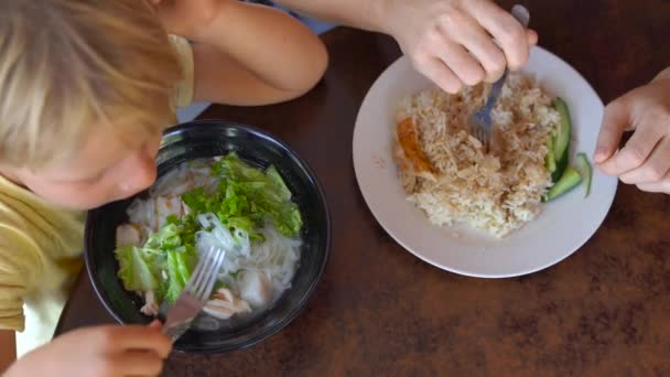 Top view of little boy with young woman eating asian dishes at table.