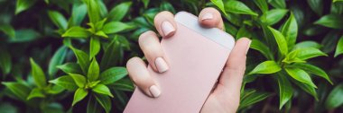 Hands with Pink Nails Hold Pink Phone. BANNER, long format