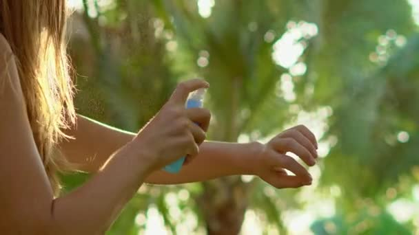 Woman spraying insect repellent on skin outdoor at daytime