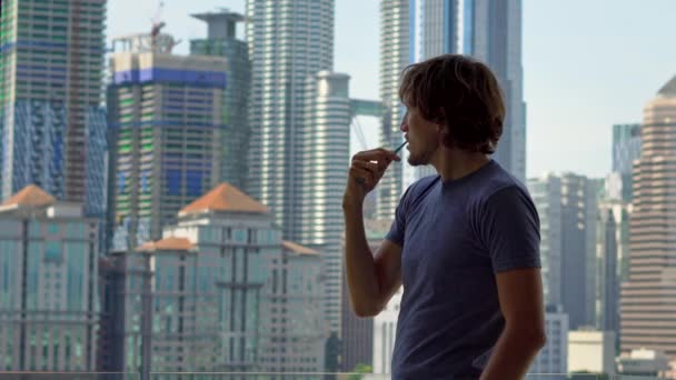 Young man brushing teeth standing near window with city-view