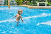 Fotografie Young boy kid child splashing in swimming pool having fun leisure activity.