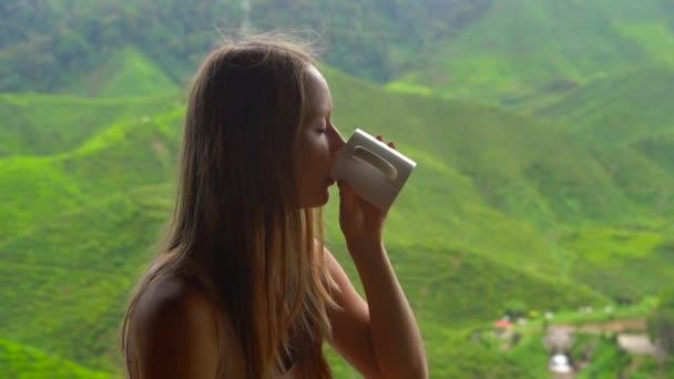 Zpomaleně snímek mladé ženy, posezení v kavárně s výhledem na Vysočině čajové terasy a pití čaje