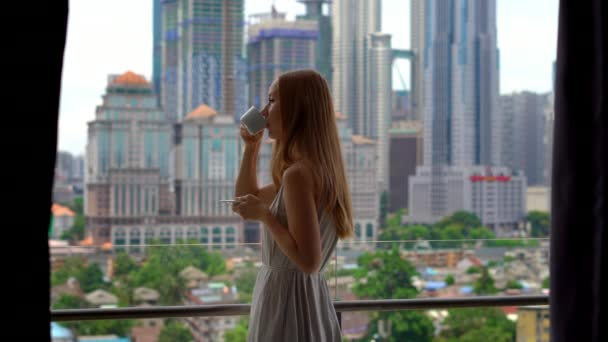 Young woman on a balcony of her apartment with a view on a city centre full of skyscrappers drinks morning coffee.