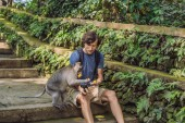 Young man using selfie stick for taking selfie with funny macaque monkey in woods of Bali.