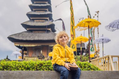 Boy sitting with musical instrument near Pura Ulun Danu Bratan water temple in Bali, Indonesia
